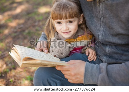 Daddy daughter reading a book outdoors