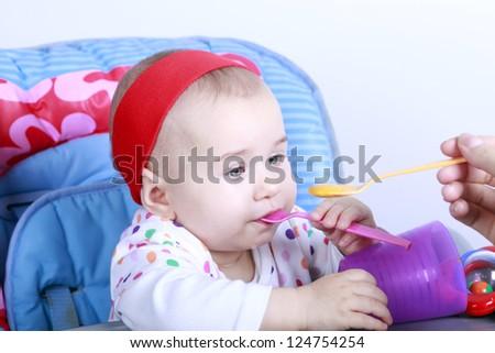 Daddy feeding his baby girl - stock photo