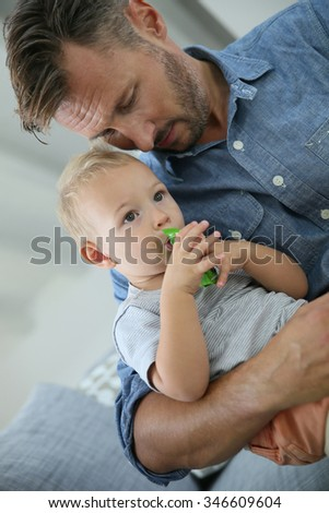 Daddy holding baby boy while eating snack