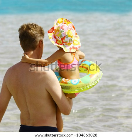 Daddy keeps little daughter on hands and going to swim in the ocean - stock photo