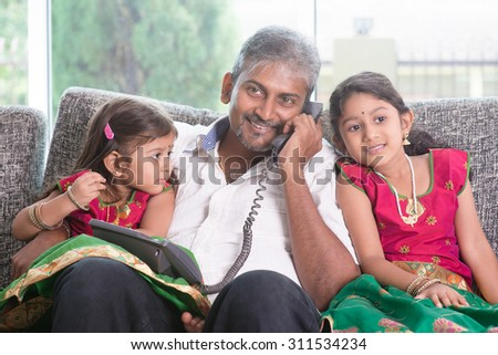 Daddy  making a phone call to mommy while taking care of children at home. Asian Indian family at home. - stock photo