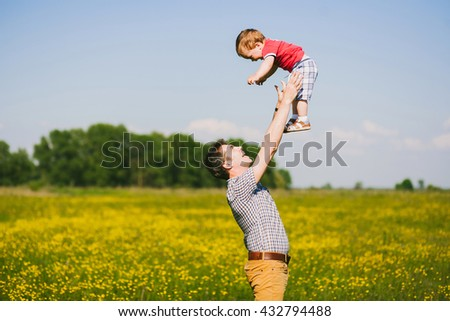 Daddy playing with his little sun outside at beautiful nature landscape. People having fun outdoors on sunny spring or summer day. Happy family of father and child. Happy boy in strong hands of father - stock photo