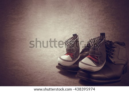 Daddy's boots and baby's sneakers, on wood background, fathers day concept.vintage color - stock photo