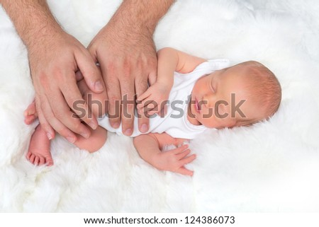 Daddy's hands on a newborn baby of 11 days old