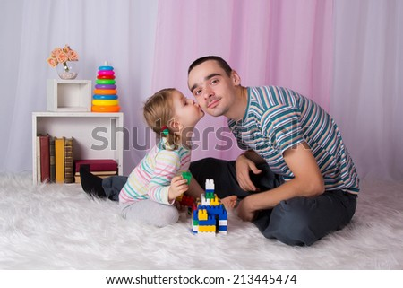Daddy's little girl kisses on the cheek, dad proud. Playtime at home - stock photo