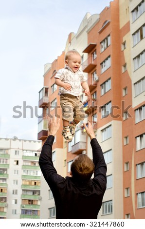 daddy tossing his infant son up on background of apartment houses in city outdoors - stock photo