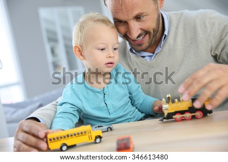 Daddy with baby playing with toy cars - stock photo