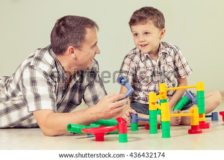 Daddy with little boy playing with toy  on the floor at the day time. Concept of friendly family.