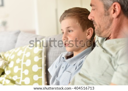 Daddy with son relaxing on sofa