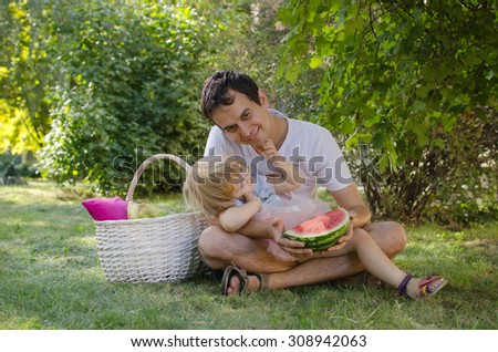 Dads with a daughter on the grass with watermelons