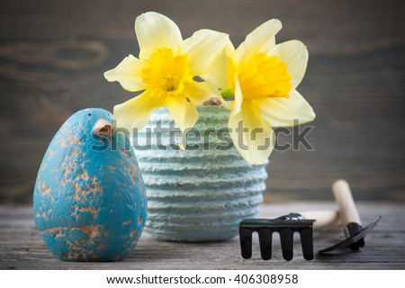 Daffodil flowers in pot with gardening tools on wooden table with blue clay bird - stock photo
