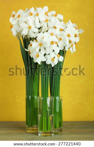 Daffodils in a glass vase on a wooden background