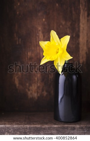 Daffodils in a glass vase on wooden shelf.