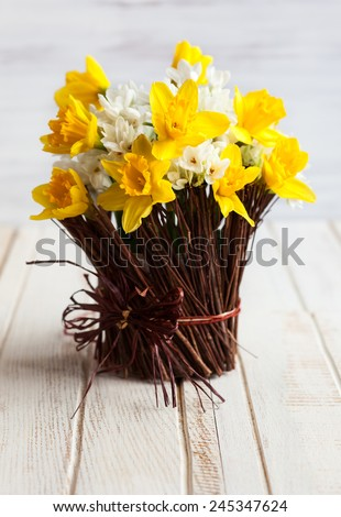 Daffodils in a twig vase on the wooden table - stock photo
