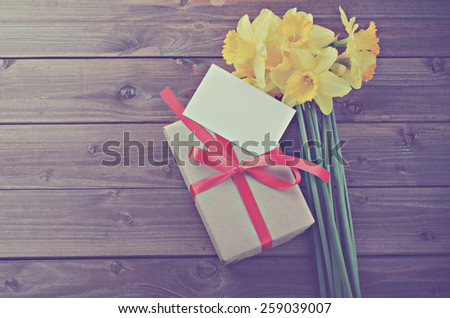 daffodils with gift box with a note on a wooden table