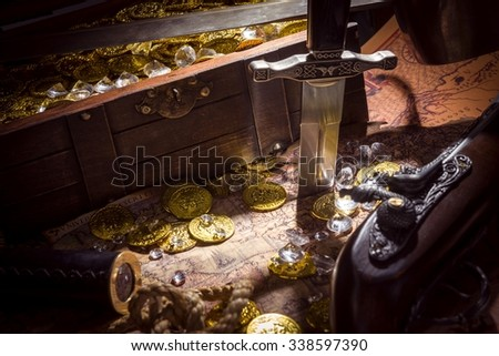 dagger, monocle, gold coins, diamonds, and a treasure chest on a treasure map - stock photo