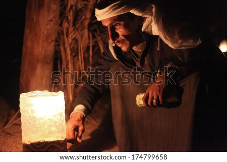DAHAB, EGYPT - JANUARY 24, 2011: Bedouin sits by the light at night. Bedouin culture still survives in the Sinai, where there is a growing appreciation of its value and its fragility. - stock photo