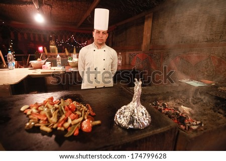 DAHAB, EGYPT - JANUARY 28, 2011: Egyptian cook stands in the kitchen. Egyptian food is a mixture of all the different civilisations that came to Egypt in the history of its existence. - stock photo