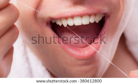 Daily health care. Young man cleaning flossing his white teeth with dental floss - stock photo