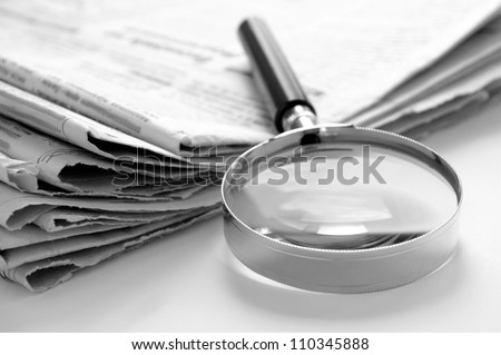 daily newspaper and a magnifying glass to find news - stock photo