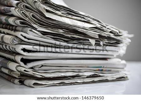 Daily newspapers stacked in a heap - stock photo