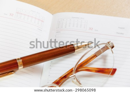 Daily planner with glasses and pen on the table. Selective focus on pen - stock photo