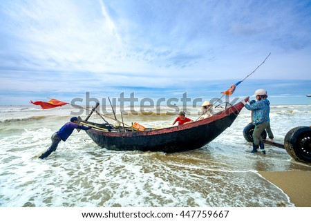 Dailylife on the beach, Vietnamese local fishermen pulling a boat up on shore in Halong Bay, Quang ninh Province, Vietnam on July 1, 2016