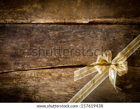 Dainty gold bow arranged diagonally in the corner on a rustic wood background of old dark textured planks with copyspace for seasonal Christmas text - stock photo
