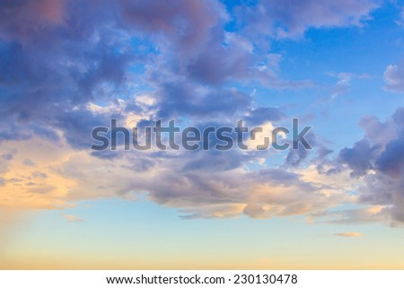 Dainty wispy pale salmon pink and golden yellow clouds at sunset background