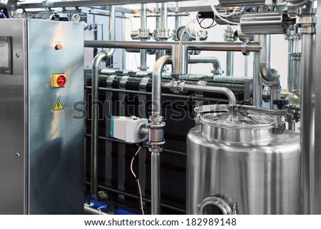 Dairy factory with milk pasteurization tank and pipes  - stock photo