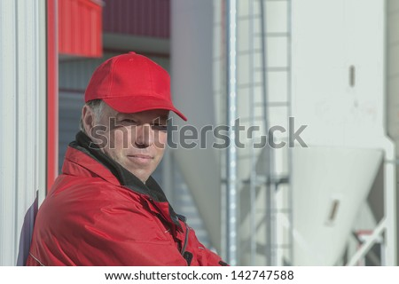 Dairy farmer posing in front of his barn - stock photo
