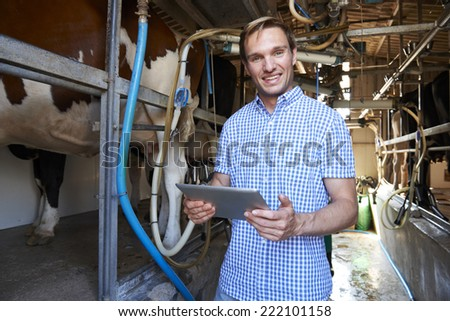 Dairy Farmer Using Digital Tablet In Milking Shed - stock photo