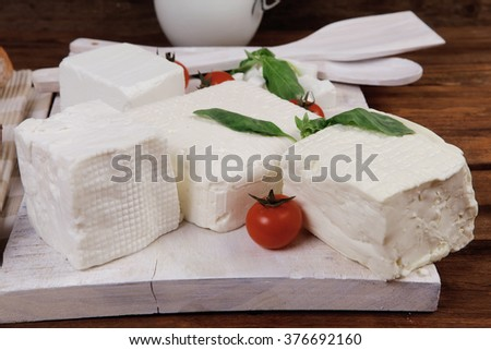 dairy food fresh white greek goat sheep feta cheese on plate with milk in pitcher cherry tomatoes french bun over dark wooden table - stock photo