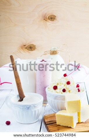 Dairy produce. Milk in bottle, cottage cheese in bowl, kefir in jar, cranberry yogurt in glass, sour cream in cup, butter and fresh berries. Wooden white table.