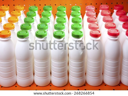 dairy products bottles with bright covers on a shelf in the shop - stock photo
