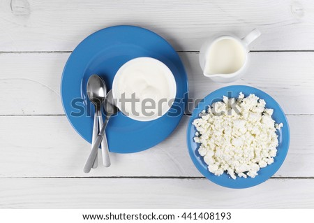 Dairy products: cottage cheese, milk and sour cream in blue dishware on white wooden table. Top view point.