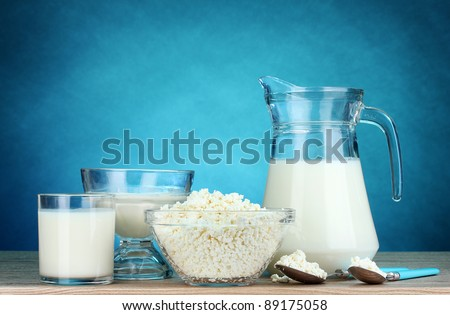 Dairy products on wooden table on blue background