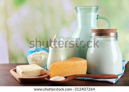 Dairy products on wooden table, on green nature background