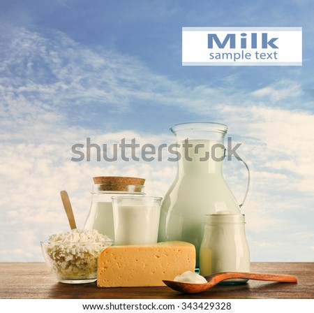 Dairy products on wooden table on sky background