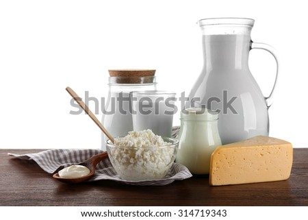 Dairy products on wooden table on white background