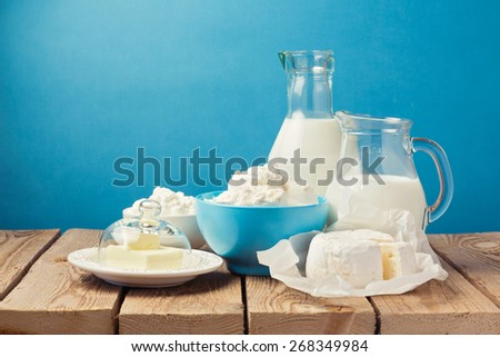 Dairy products on wooden table over blue background - stock photo