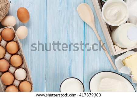 Dairy products on wooden table. Sour cream, milk, cheese, egg, yogurt and butter. Top view with copy space - stock photo