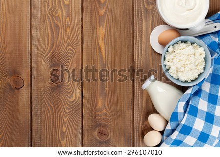 Dairy products on wooden table. Sour cream, milk, cheese, eggs, yogurt and butter. Top view with copy space - stock photo