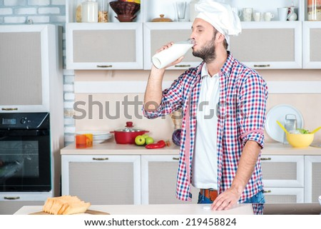 Dairy. Young male chef drinking a bottle of milk while standing in the kitchen and milkman smiling at the camera - stock photo