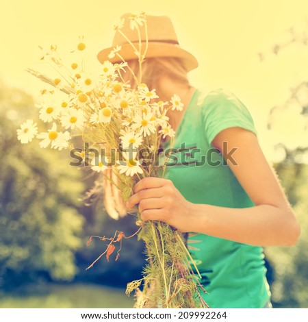 Daisies of the girl in his hand on a sunny warm day - stock photo