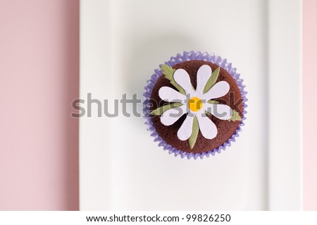 Daisy flower cupcake on a plate from above