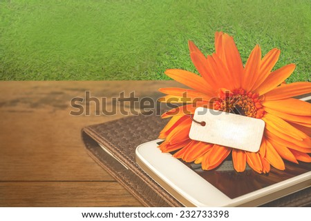 daisy flower on and smartphone on wooden table and garden vintage color tone.