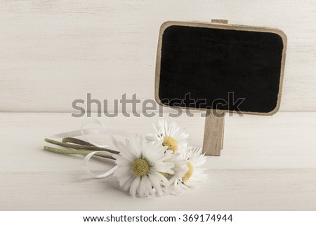 daisy flowers and chalkboard on wooden surface - stock photo