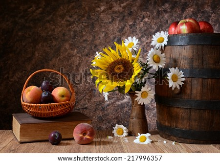 Daisy flowers in a vase with fresh fruits in a vicker basket on a wodden table