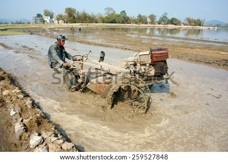 DAK LAK, VIET NAM- FEB 25: Asian farmer working on rice field, Vietnamese man plough paddy plantation for new crop by tractor, repair soil for sow rice in hot day, Daklak, Vietnam, Feb 25, 2015